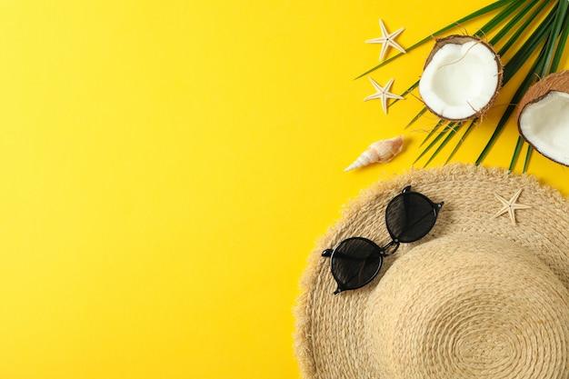 麦わら帽子、サングラス、ヒトデ、ココナッツ、ヤシの葉のテキストとトップビューの色背景スペース。夏休みのコンセプト