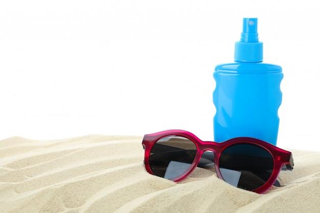 白い背景に分離された澄んだ海の砂の上にサングラスと日焼け止め。夏休み
