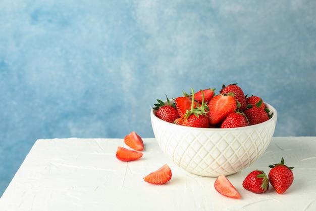 Шар с свежими клубниками на белой таблице против голубой предпосылки, космоса для текста. летние сладкие фрукты и ягоды