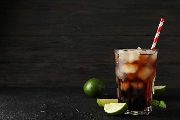 冷たいコーラと黒セメントの背景にライムのガラス