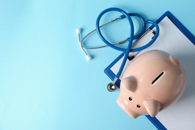 青色の背景、テキスト用のスペースに聴診器と貯金箱