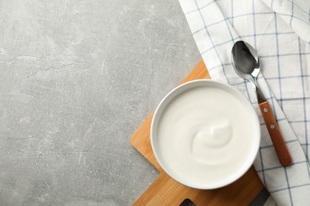 Композиция с йогуртом в миске на сером фоне