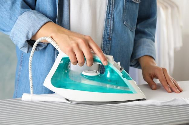 Молодая женщина гладит рубашку на гладильной доске, крупным планом