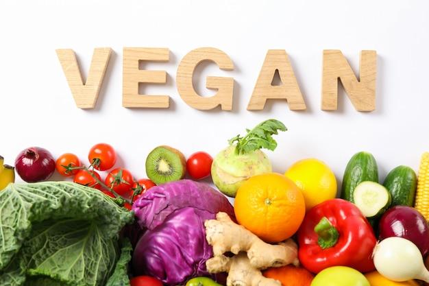 Слово веганский, разные овощи и фрукты, изолированные на белом