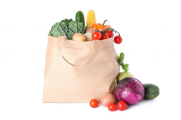 Большая сумка с разными овощами на белом фоне