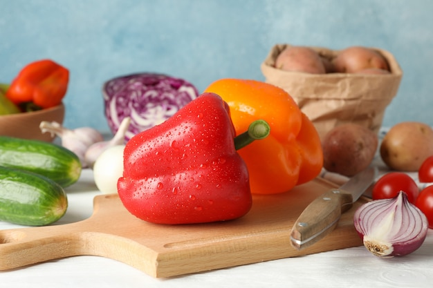 Овощи, доска и нож на белом деревянном фоне крупным планом