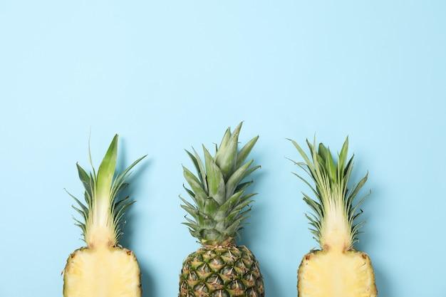 Верхняя часть ананасов на сини, взгляд сверху. сочные фрукты