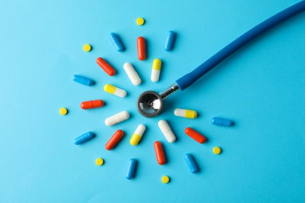 丸薬と青、トップビュー、テキスト用のスペースに聴診器でフラットレイアウト