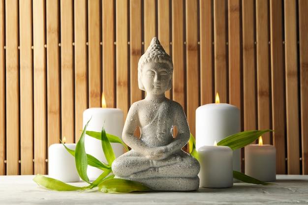 Будда и свечи на белом деревянном столе. концепция дзен