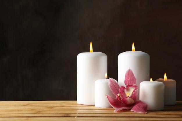 Свечи и орхидеи на бамбуковом столе. концепция дзен