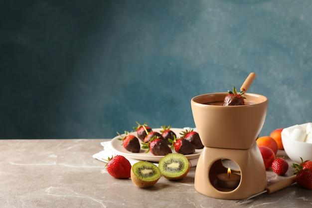 Композиция с ингредиентами для шоколадного фондю на сером столе. готовить фондю