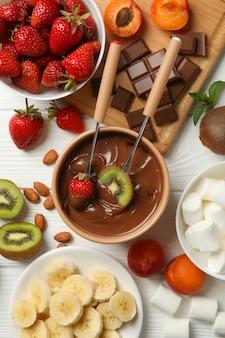 Композиция с ингредиентами для шоколадного фондю на белом фоне деревянные. готовить фондю