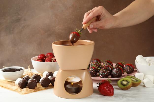 Женщина окуная клубника в шоколаде. вкусное шоколадное фондю