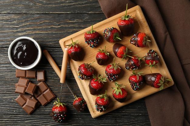 Шоколадное фондю. клубника в шоколаде на деревянном фоне, вид сверху