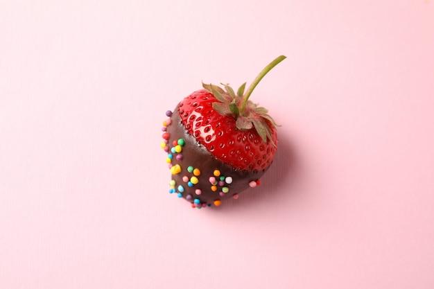 Шоколадное фондю. клубника в шоколаде на розовом фоне