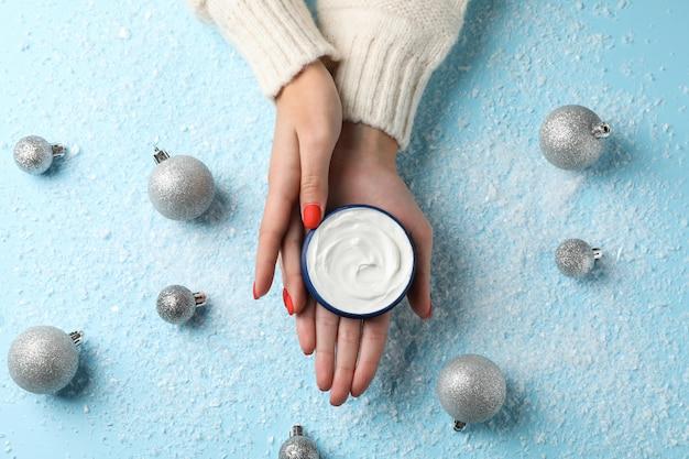 Женщина в свитере держит в руках баночку с кремом, увлажняющий крем для чистой и мягкой кожи в зимнее время, новогодняя игрушка на снежно-голубом, место для текста. вид сверху