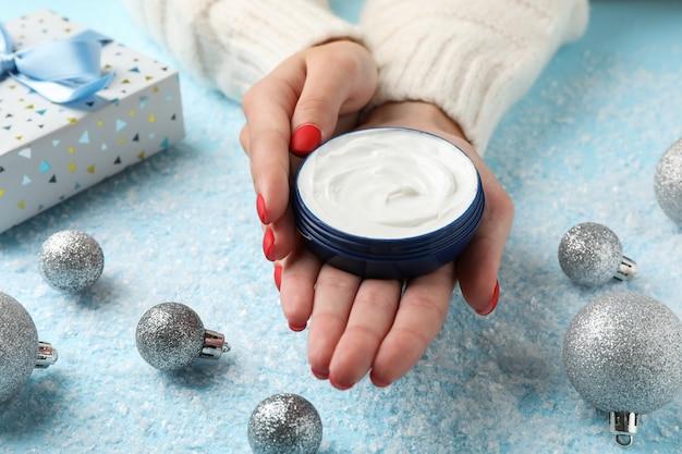 Женщина в свитере держит в руках баночку с кремом, увлажняющий крем для чистой и мягкой кожи в зимнее время, елочные игрушки, подарочные коробки на снежно-голубом, место для текста. крупный план