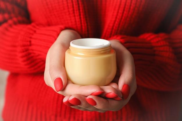 Женщина, держащая банку увлажняющего крема, крупным планом. зимняя косметика. пространство для текста