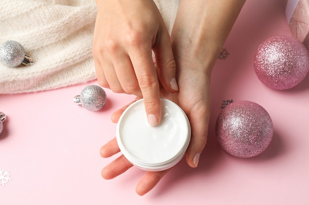 クリームの瓶、ピンク、テキスト用のスペースに暖かいセーターを保持している女性。閉じる
