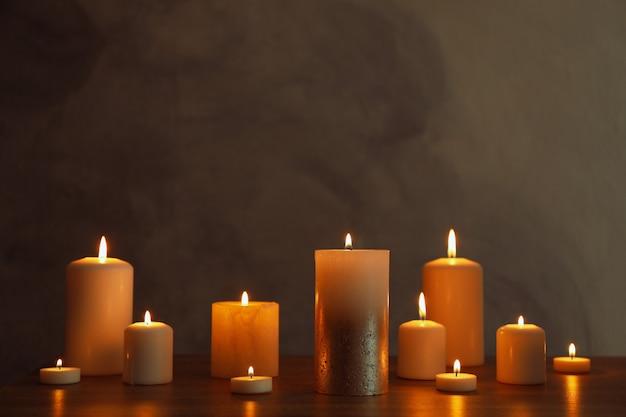 Группа горящих свечей на черном столе