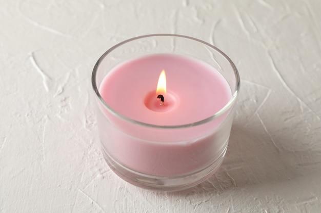 Розовая свеча в стеклянной банке на белом, крупный план