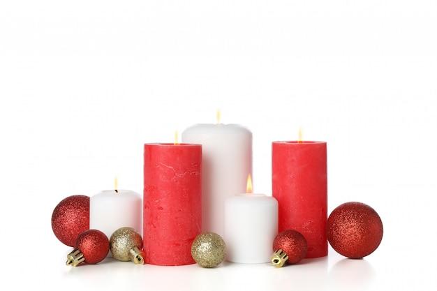 キャンドルと白で隔離されるクリスマスボール