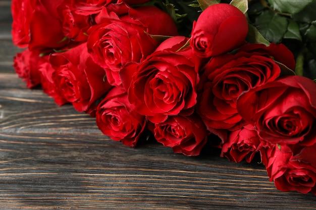 木製の背景に赤いバラの花束をクローズアップ