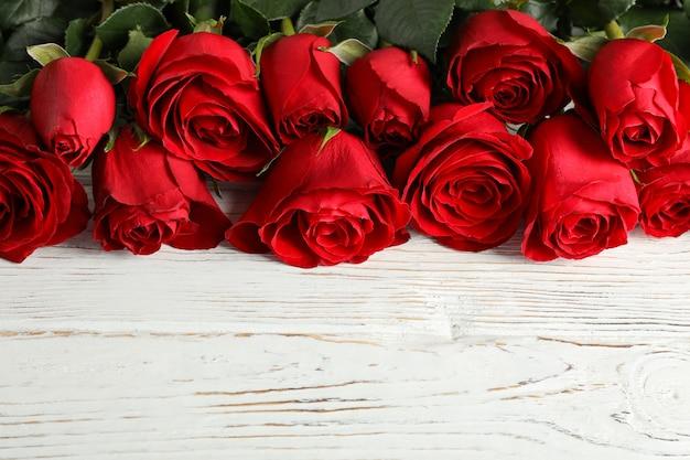 白い木製の素朴な背景に美しいバラの花をクローズアップ