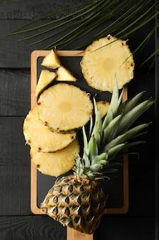 Разделочная доска с ананасом и пальмовая ветвь на деревянном фоне, вид сверху