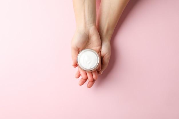 Женщина, держащая банку зимнего крема для кожи на розовом