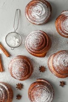 Булочки с корицей с сахарной пудрой и стеками корицы на сером