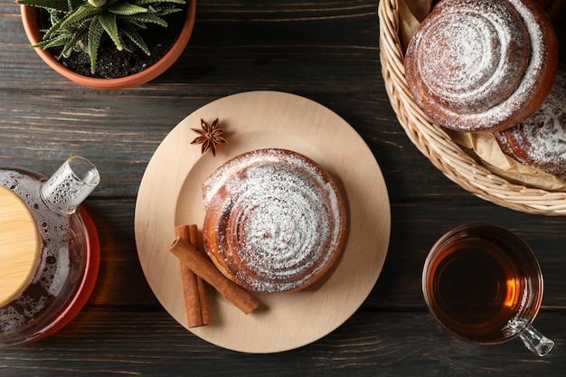 Булочки с корицей, чай и растения на деревянные