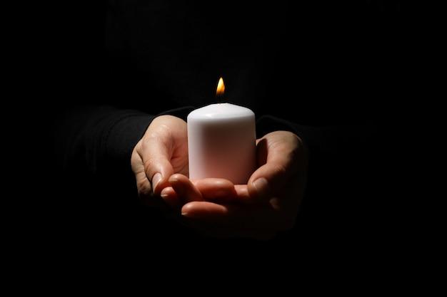 Женщина держит свечу на черном