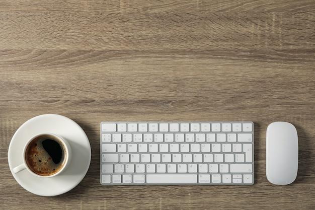 Рабочее место. клавиатура, мышь и чашка кофе на деревянном, место для текста