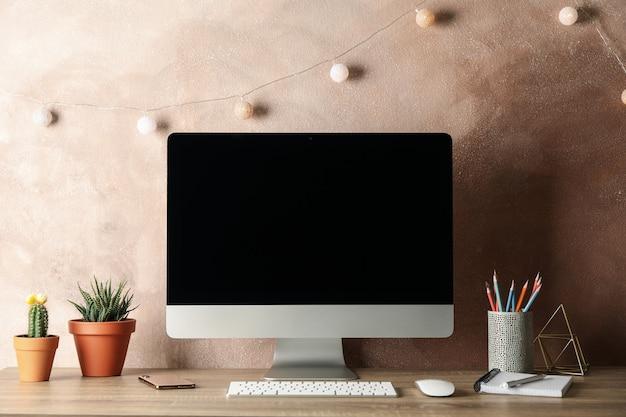 コンピューター、植物、木製のテーブルに電話のある職場。ライト・ブラウン