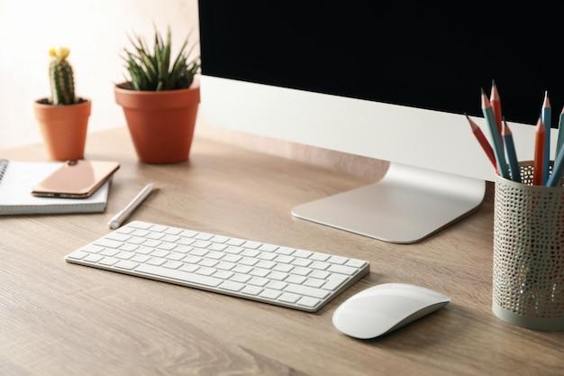 コンピューターと木製のテーブルの上の植物と職場をクローズアップ
