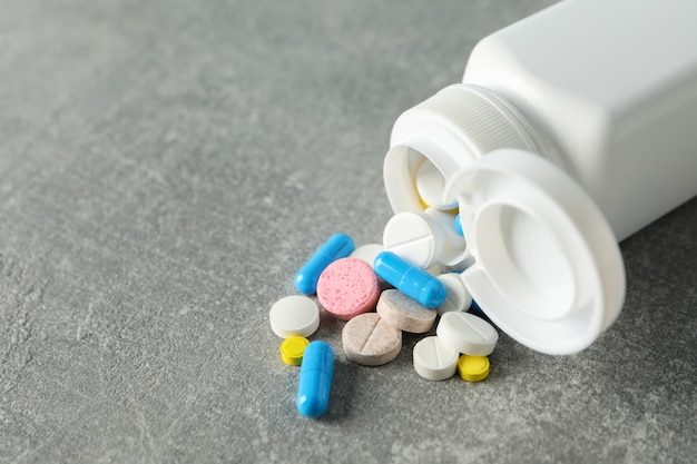 医療用コンテナーと灰色の背景上の丸薬をクローズアップ