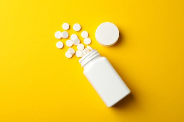 空白の医療ボトルと黄色の背景、トップビューでの丸薬
