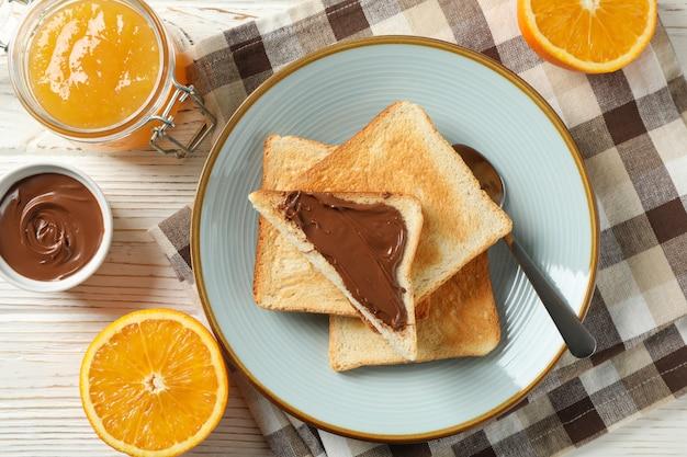 Тарелка с тостами, апельсин, джем, шоколадный крем и полотенце на фоне дерева, вид сверху