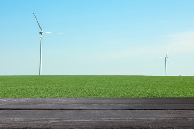 風車のあるフィールドに対して木製のテーブル。農業のコンセプトです。モックアップ