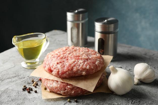 Специи и бумага для выпечки с мясным фаршем на сером, крупным планом