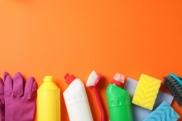 オレンジ色の背景、テキスト用のスペースに洗剤とクリーニング用品のボトル