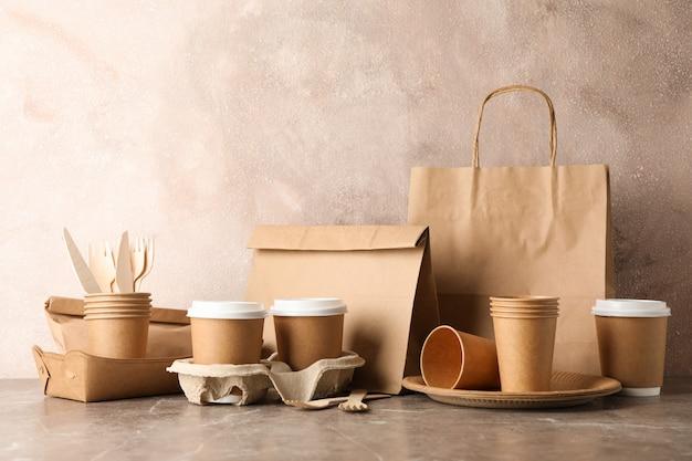 エコ-フレンドリーな食器と灰色のテーブル、テキスト用のスペースの紙袋
