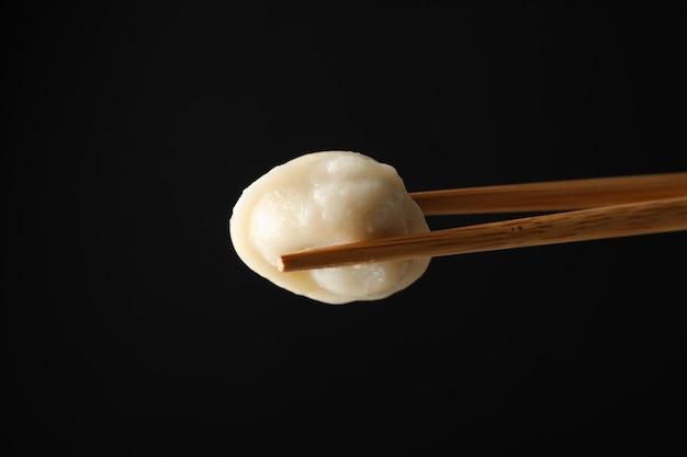 黒の背景に餃子と箸をクローズアップ