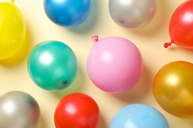 Разноцветные воздушные шары на бежевом фоне, вид сверху