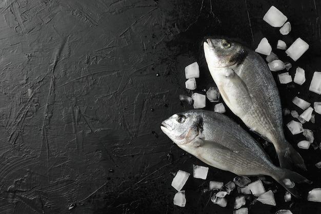 ドラドの新鮮な魚と黒の背景、上面に氷