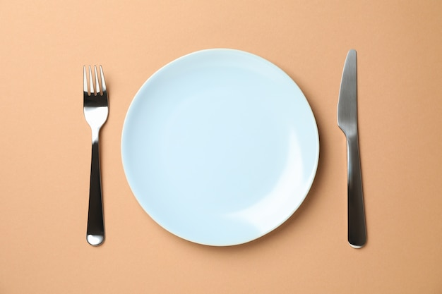 Сервировка стола. тарелка, вилка и нож на фоне ремесла, вид сверху