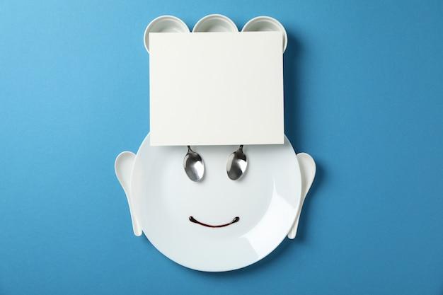 Лицо шеф-повара из столовых приборов и посуды на синем фоне, место для текста