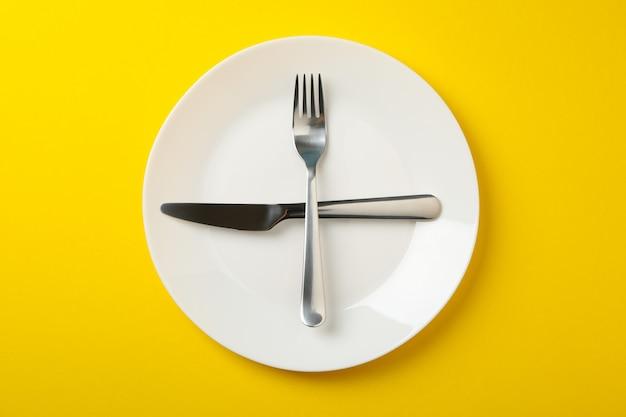 Тарелка с вилкой и ножом на желтом фоне, вид сверху