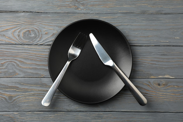 Тарелка с вилкой и ножом на деревянном фоне, вид сверху